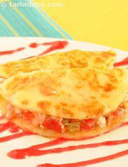 Stuffed Malpuas with Paneer and Strawberry in Saffron Syrup